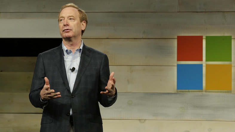 Brad Smith, Microsoft Corp.'s General Counsel and Executive Vice President of Legal and Corporate Affairs, greets attendees at Microsoft Corp.'s annual shareholders meeting, Wednesday, Dec. 3, 2014, in Bellevue, Wash. (AP Photo/Ted S. Warren)