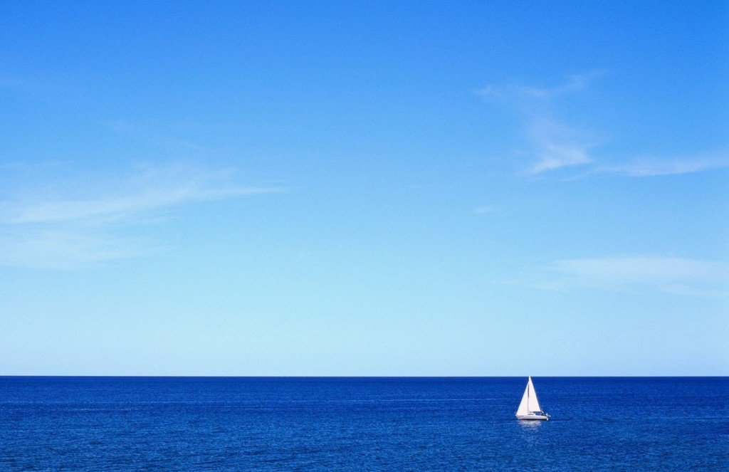 sailboat_in_the_middle_of_the_ocean__1680x1050