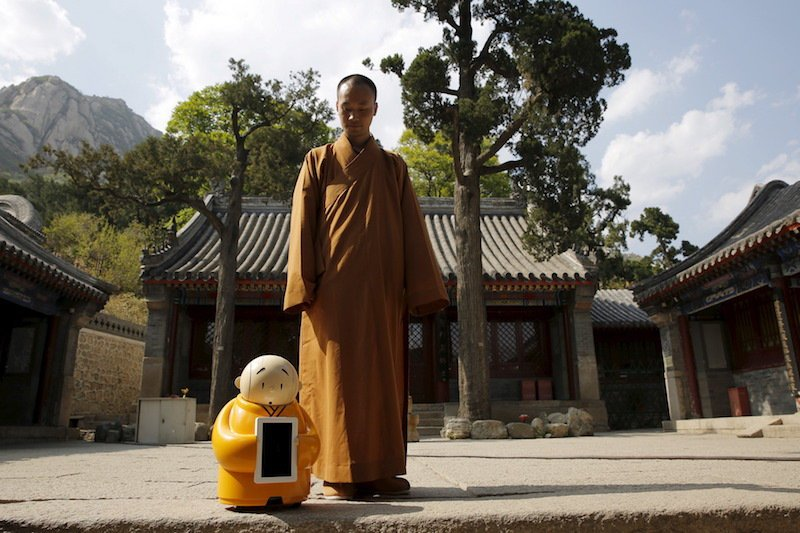 Master Xianfan looks at robot monk Xian'er as he prepares to pose for photograph in the main building of Longquan Buddhist temple on the outskirts of Beijing