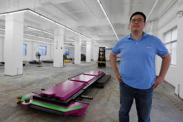 "Marco Wu, CEO of Shenzhen Yeefung Automation Technology Co Ltd, poses with a laser-guided ""parking robot"", at a research and development centre in Shenzhen, China June 29, 2016. REUTERS/Bobby Yip"