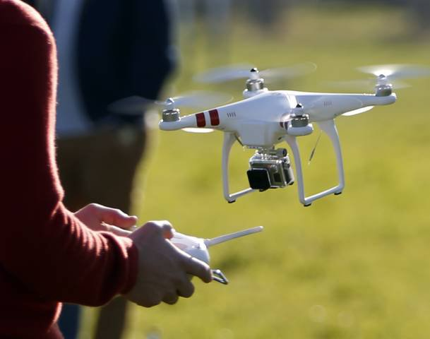 A pilot flies a Phantom drone by DJI company at the 4th Intergalactic Meeting of Phantom's Pilots in an open secure area in the Bois de Boulogne, western Paris