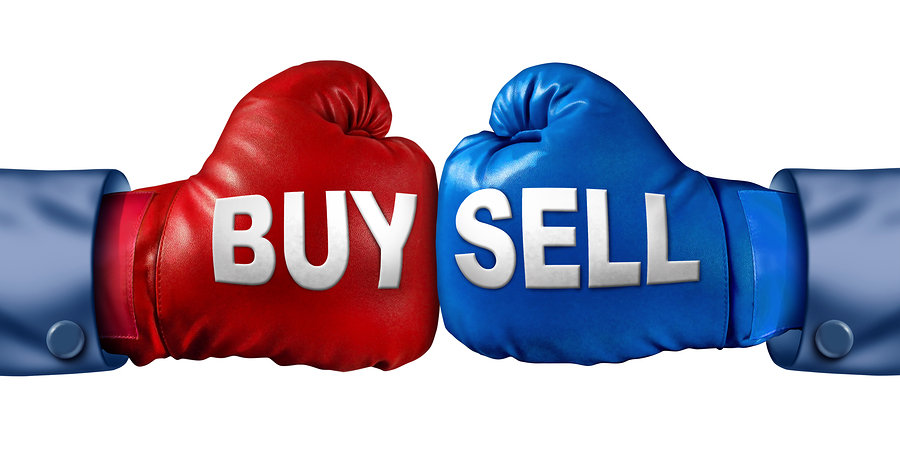 Buy or sell stocks or shares in a business as a boxing match in the symbolic financial ring of investing with two gloves fighting for trading direction in the stock market isolated on a white background.
