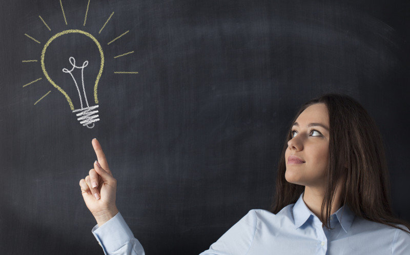Big glowing light bulb on blackboard with businesswoman hand pointing it